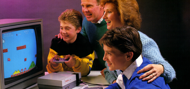Glad 80-talsfamilj (mamma, pappa och två söner) tittar på när en av sönerna spelar nintendo.